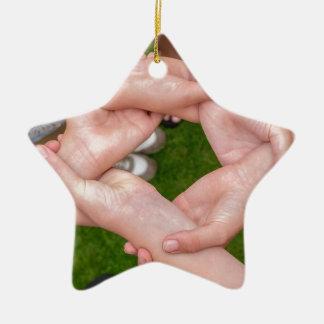 Arme mit den Händen der Mädchen, die sich halten Keramik Stern-Ornament