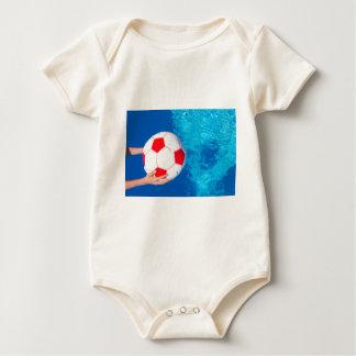Armholding-Wasserball über Swimmingpoolwasser Baby Strampler