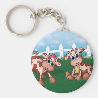 Baby-Kühe auf einer Hügel-Seite mit weißer Schlüsselanhänger