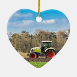 Bauer auf dem Traktor, der sandigen Boden im Keramik Ornament