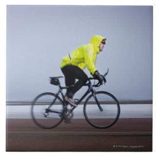 Bemannen Sie Fahrräder an einem kalten und Große Quadratische Fliese