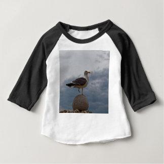 Betrügen Sie mit einem Bein auf einem Ball des Baby T-shirt