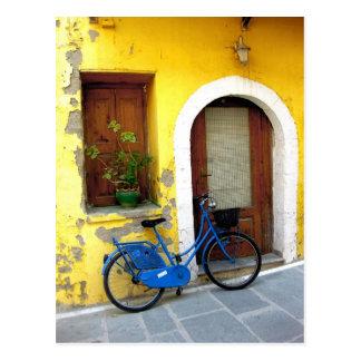 Blaues Fahrrad gegen eine gelbe Wand Postkarte