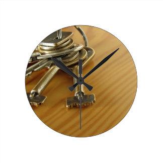Bündel abgenutzte Hausschlüssel auf hölzerner Runde Wanduhr
