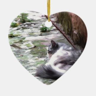 Das flaumige Katzenschlafen ducken sich auf dem Keramik Herz-Ornament