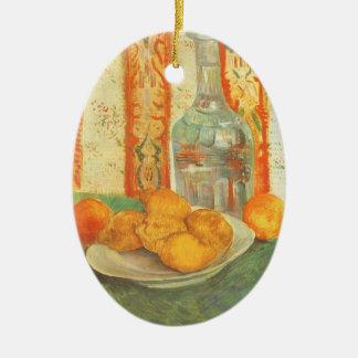 Dekantiergefäß und Zitronen auf einer Platte durch Keramik Ornament