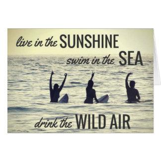 Die Mädchen, die Brandungs-Strand surfen, trinken Karte