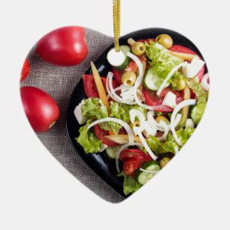 Draufsicht einer kleinen Platte des rohen Salats Keramik Herz-Ornament