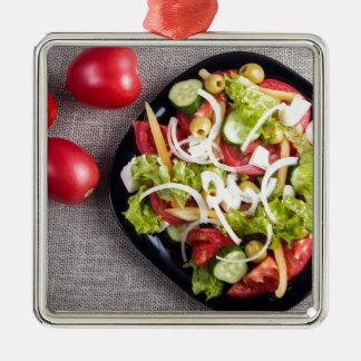 Draufsicht einer kleinen Platte des rohen Salats Quadratisches Silberfarbenes Ornament