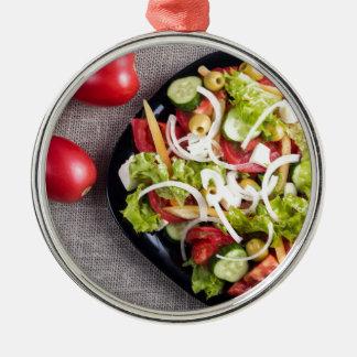 Draufsicht einer kleinen Platte des rohen Salats Rundes Silberfarbenes Ornament