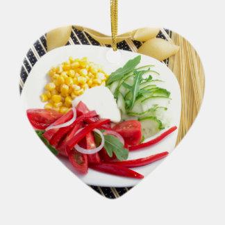 Draufsicht einer weißen Platte mit Salat Keramik Herz-Ornament