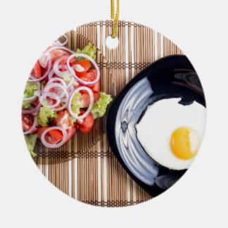 Draufsicht über ein Spiegelei und einen Salat der Keramik Ornament