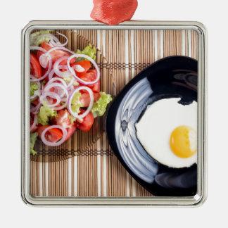 Draufsicht über ein Spiegelei und einen Salat der Quadratisches Silberfarbenes Ornament