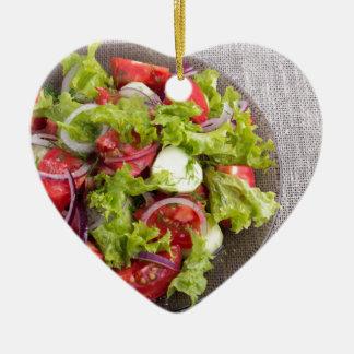 Draufsicht über eine Platte mit frischem Salat des Keramik Herz-Ornament