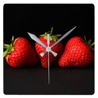 Drei Erdbeeren auf Wanduhr des Schwarz-(H)