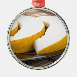 Drei Scheiben saftige gelbe Melone Rundes Silberfarbenes Ornament