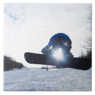 Ein weiblicher Snowboarder nimmt Luft im New Große Quadratische Fliese