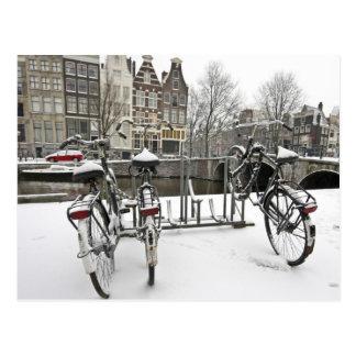 Fahrräder in schneebedecktem Amsterdam in den Postkarte