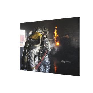 Feuerwehrmänner löschen ein Feuer in einem Leinwand Drucke
