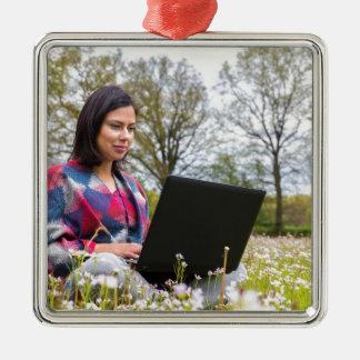 Frau sitzt mit Laptop in blühender Wiese Quadratisches Silberfarbenes Ornament