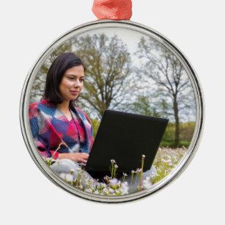Frau sitzt mit Laptop in blühender Wiese Rundes Silberfarbenes Ornament