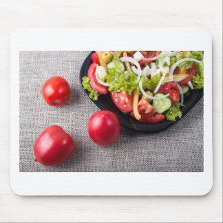 Frische Tomaten und ein Teil einer Platte Mousepads