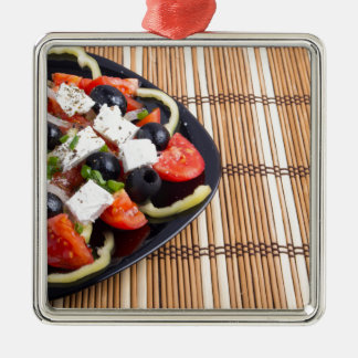 Frischer vegetarischer Salat in einer schwarzen Quadratisches Silberfarbenes Ornament