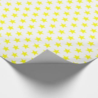 Fröhliche und helle gelbe Sterne am weißen Geschenkpapier