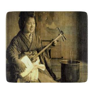 Geisha, der das Shamisen Vintages altes Japan übt Schneidebrett
