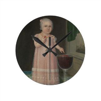 Gruseliges kleines Mädchen isst Süßigkeit Runde Wanduhr