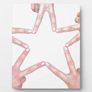 Hände der Mädchen, die Stern machen, formen auf Fotoplatte