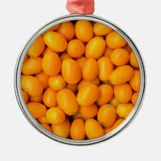 Haufen der orange japanischer Orangen im Rundes Silberfarbenes Ornament