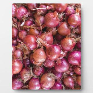 Haufen der roten Zwiebeln auf Markt Fotoplatte