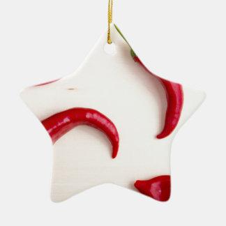 Heiße Chili-Paprikaschoten auf einem hellen Keramik Stern-Ornament