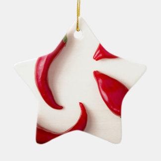 Heiße rote Chili-Paprikaschoten auf einem hellen Keramik Ornament