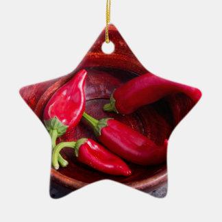 Heiße rote Chili-Paprikaschoten auf einem Keramik Stern-Ornament