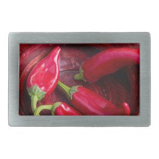 Heiße rote Chili-Paprikaschoten auf einem Rechteckige Gürtelschnallen