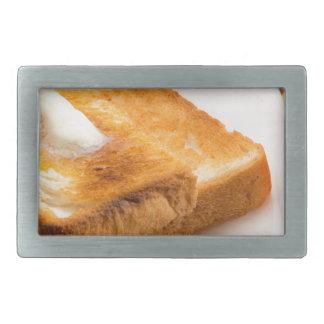 Heißer Toast mit Butter auf einer weißen Platte Rechteckige Gürtelschnalle