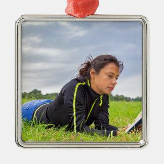 Junge Frau, die im Graslesebuch liegt Quadratisches Silberfarbenes Ornament