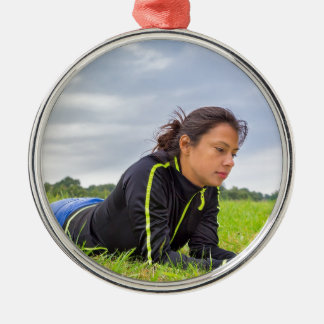 Junge Frau, die im Graslesebuch liegt Rundes Silberfarbenes Ornament