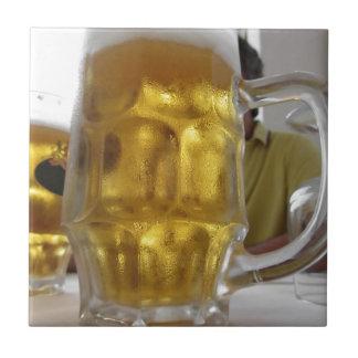 Kalte Tasse helles Bier auf der Tabelle an einem Kleine Quadratische Fliese