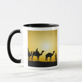 Kamele und Kamelfahrer silhouettiert am Tasse