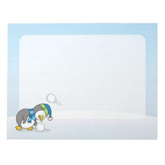 Kleiner Pinguin, der einen Schneeball erhält Notizblock