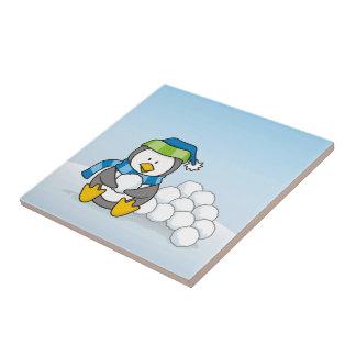 Kleiner Pinguin, der mit Schneebällen sitzt Kleine Quadratische Fliese