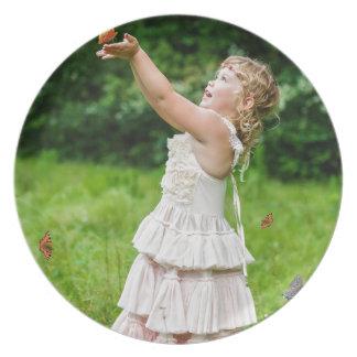 Kleines Mädchen, das ein Butterly fängt Flache Teller