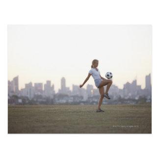 Kneeing Fußball der Frau im städtischen Park Postkarte