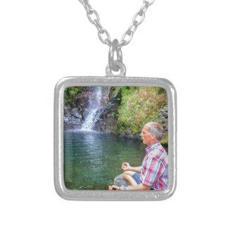 Mann, der auf dem Felsen meditiert nahe Wasserfall Versilberte Kette