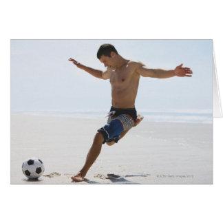 Mann, der Fußball auf Strand tritt Karte