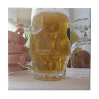 Männliche Hand, die eine kalte Tasse helles Bier Keramikfliese