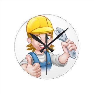 Mechaniker-oder Klempner-Frau, die Schlüssel hält Wanduhr